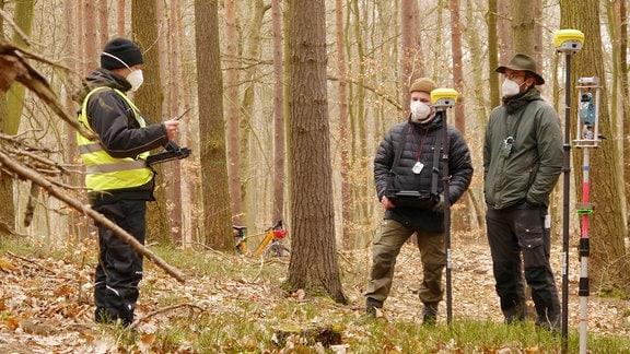 drei Männer stehen mit Messgeräten im Wald