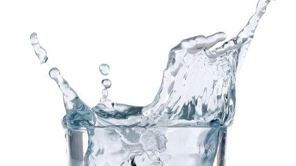 Ein Eiswürfel fällt in ein Glas mit Wasser.