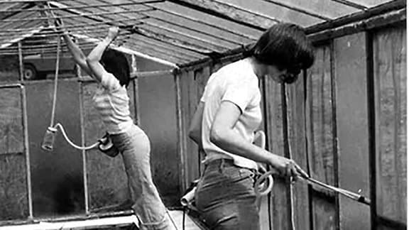 Schwarz-weiß Aufnahme von zwei Personen, die in einer Art Gewächshaus über einem Bachlauf stehen und Sauggeräte in der Hand haben