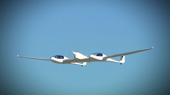 Ein weißes Flugzeug vor blauem Himmel.