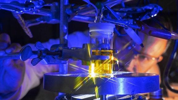 Ein Mann betrachtet in einem Labor ein Gefäß mit Flüssigkeit, welches in eine Apparatur eingespannt ist.