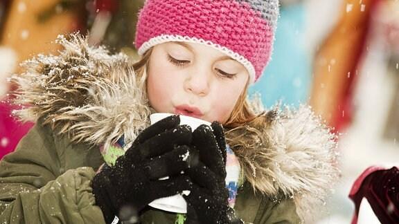 Ein Mädchen wärmt sich an einer heißen Tasse