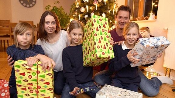 Eine fünfköpfige Familie sitzt mit Geschenken vor einem Weihnachtsbaum