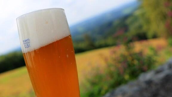 Ein Glas mit Weizenbier vor dem hügeligen Panorama des Bergischen Landes in der Nähe von Eckenhagen