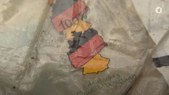 """Nahaufnahme einer Verpackung mit Deutschlandkarte in schwarz-rot-gold und der Aufschrift """"100% deutsches Qualitätsgeflügel"""""""
