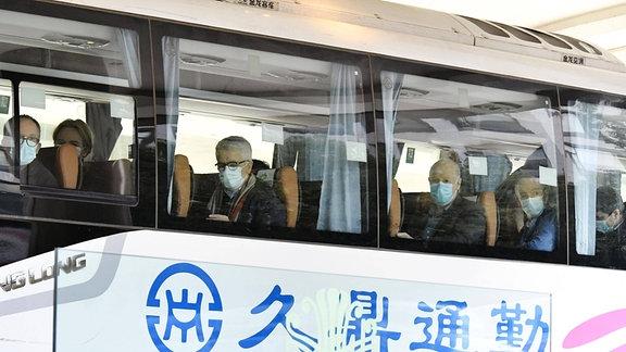 WHO-Mitarbeiter sitzen mit Maske in einem Bus in Wuhan.