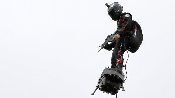 Ein Mann schwebt in der Luft auf einem ''Flyboard''.