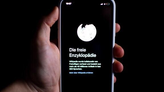 Eine Hand hält ein Smartphone mit der Wikipedia App
