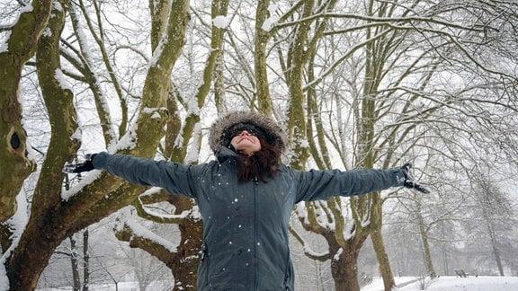 Eine Frau ist mit dicker Winterjacke und Handschuhen gegen die Kälte gerüstet und genießt das Schneewetter.