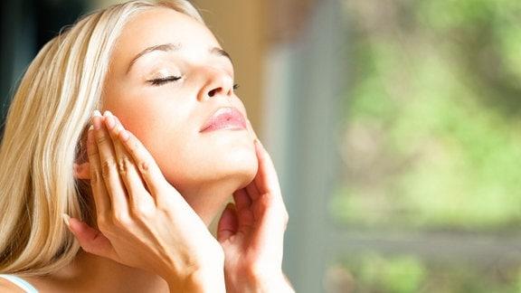 Eine Frau streicht mit ihren Händen über ihr Gesicht.