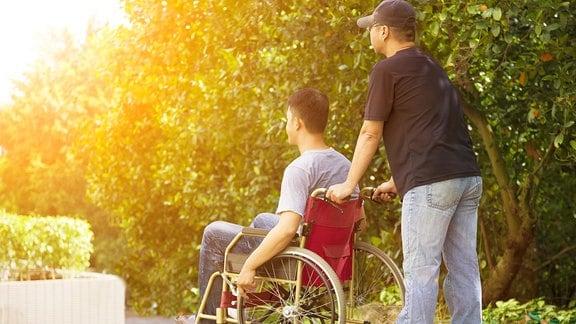 Ein junger Mann sitzt im Rollstuhl und wird geschoben.