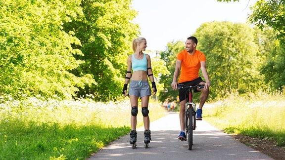 glückliches Paar mit Rollschuhen und Fahrrad