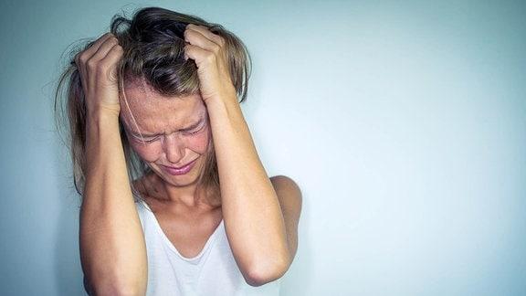 Eine junge Frau mit Händen in den Haaren.