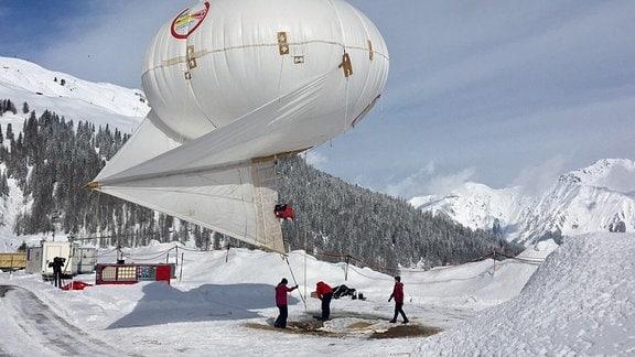 Drei Männer in roten jacken stehen in den Bergen auf einem Schneefeld und bereiten einen großen, weißer Wetterballon vor