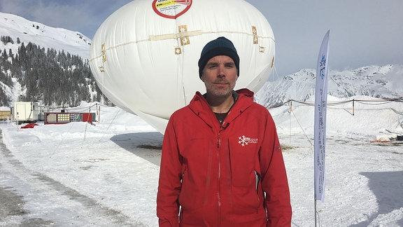 Ein Mann mit roter Jacke und schwarzer Mütze und vor dem etwa Manngroßen weißen Wetterballon
