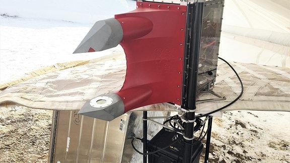 Detailaufnahme eines rot lackierten technischen Geräts, das auf einem Tosch in einem Zelt liegt. Es handelt sich um eine holografische Kamera.