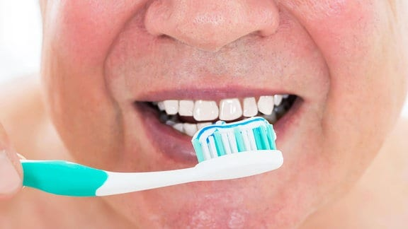 Ein Mann putzt seine Zähne.
