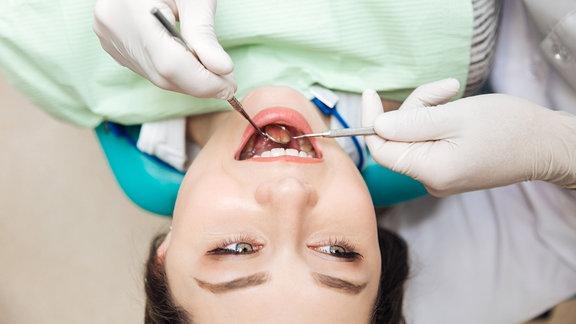Patientin mit geöffnetem Mund während einer Zahnuntersuchung