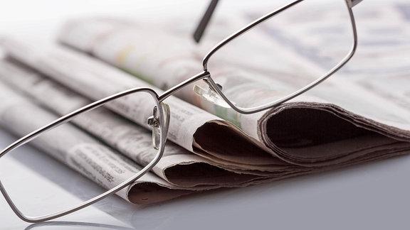 Eine Brille auf Zeitungen