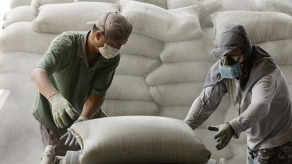 Arbeiter greifen nach einem Sack Zement.