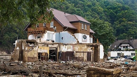 Ländliches Hotel im Ahrtal: Oberer Teil unversehrt, untere Etage verwüstet mit viel Schutt; im Hintergrund Wald