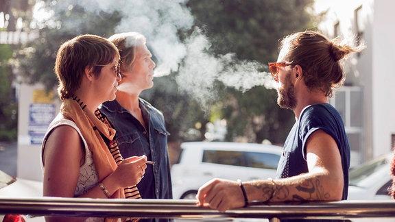Drei Personen stehen rauchend zusammen.