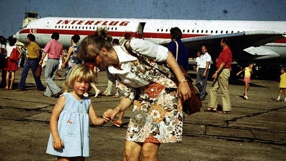 Frau und Kind vor Flugzeug