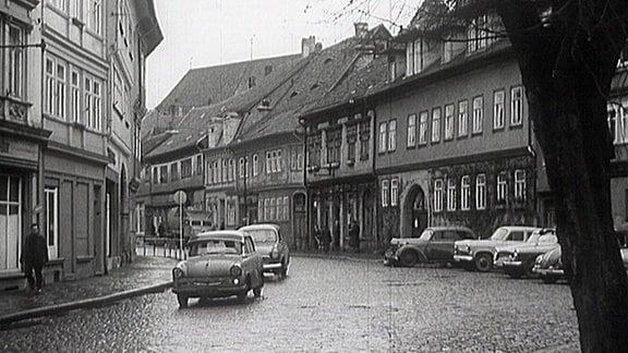 Ein Trabant und ein Wartburg fahren auf einer verregneten Straße in Arnstadts Innenstadt im Jahr 1967.