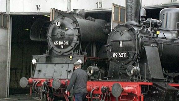 Zwei Dampflokomotiven stehen in Reparaturhalle