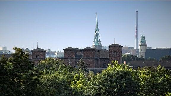 """Justitz-Vollzugsanstalt Halle - umgangssprachlich wegen der rötlichen Ziegel und Klinker auch """"Roter Ochse"""" genannt. Architektonisch ein Widerspruch zur Marktkirche und dem Roten Turm im Hintergrund der Aufnahme. Halle, Juli 2014"""