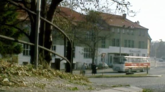 Bus fährt in einem Ort an Menschen und einem Haus vorbei.