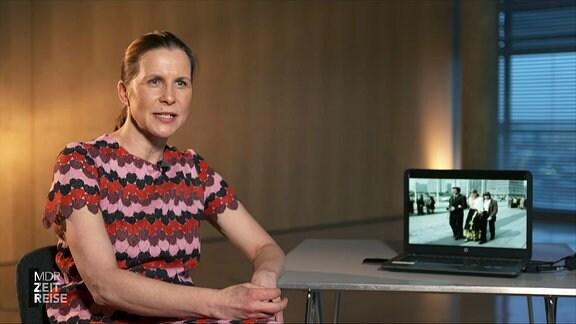 Eine Frau sitzt vor einem Tisch mit einem Laptop