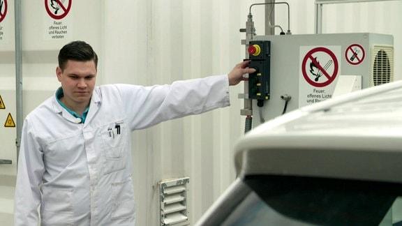 Mann in Laborkittel bedient Maschine in einer Fabrikhalle.