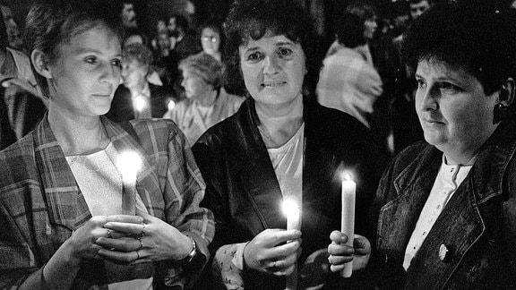 Im Herbst 1989 stehen im Anschluss an ein Friedensgebet Teilnehmer mit Kerzen in der Hand vor der Nikolaikirche in Leipzig.