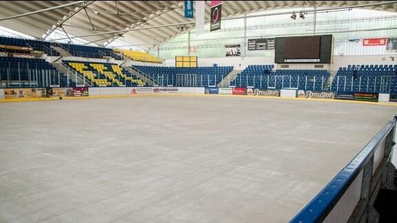 Eissporthalle Chemnitz. Im Vordergrund Eisfläche, im Hintergrund blau-gelbe Besucherränge