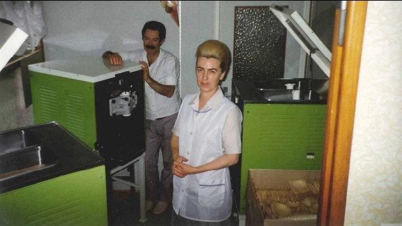 """Chefin Karin Winter und ein Mitarbeiter befüllen Softeis-Maschinen in der """"Eishalle"""" an der Kaßberg-Auffahrt in Karl-Marx-Stadt, Aufnahme aus den 1980er-Jahren"""
