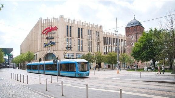 """Einkaufspassage """"Galerie Roter Turm"""" mit Schriftzügen von """"Saturn"""" und """"CineStar – Der Filmpalast""""; im Vordergrund eine blaue Straßenbahn"""
