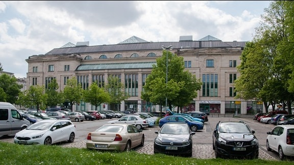 Großer, renovierter Altbau aus dem Jahre 1913. Bürokomplex; teilweise mit Glas verkleidet. Ebenerdig Ladengeschäfte. Im Vordergrund Parkplatz.