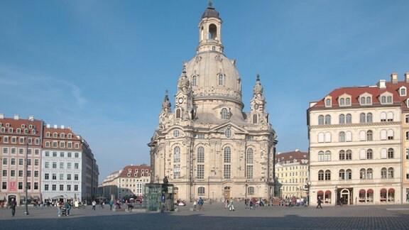 Die Sandsteinquader der wiederaufgebauten Frauenkirche zu Dresden strahlen im Sonnenschein. Viele Menschen flanieren im sanierten Altstadtzentrum rund um die Frauenkirche.