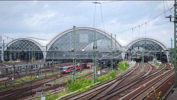Hauptbahnhof zu Dresden. Im Vordergrund Gleise. Verlaufen nach hinten. Darüber drei Glasbögen. Mittlerer größer als die anderen beiden links und rechts davon. Ein Zug verlässt den Hauptbahnhof; einer fährt gerade ein.