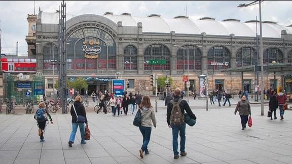 Hauptbahnhof zu Dresden seitlich. Menschen verlassen und betreten den Bahnhof.