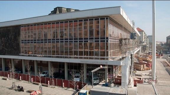 Großes, zweistöckiges Gebäude. Oberes Geschoss mit Glas verkleidet. Renovierungsarbeiten finden statt.