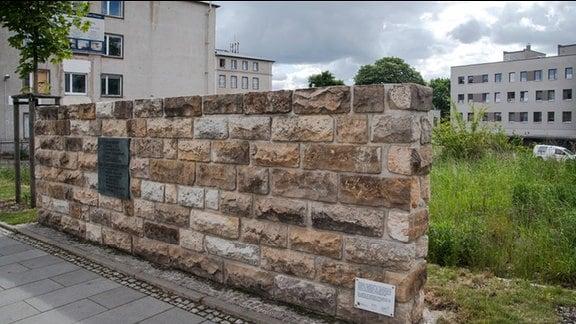 Am Grundstück der ehemaligen Dresdner Stasi-Zentrale in der Bautzner Straße steht ein Stück Mauer mit Gedenktafel. Dahinter Wiese und Häuser.