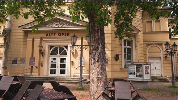 """Alte Oper in Erfurt. Eingangsbereich mit dem Schriftzug """"Alte Oper"""" darüber. Im Vordergrund: Freisitz mit Sitzgruppen, Bäume."""