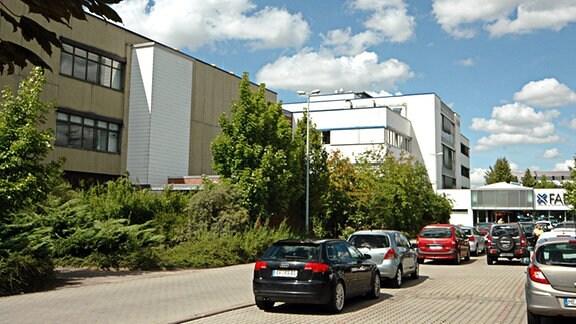 Standort des Halbleiterproduzenten X-Fab in Erfurt in der Haarbergstraße. Mehrteiliges Firmengebäude mit Flachdächern, beiger und weißen Fassaden. Im Hintergrund ist der Eingang mit dem Schriftzug XFab zu sehen. Vor den Gebäuden gitbes einen schmalen Grünstreifen mit Büschen und Bäumen. Mehrere Autos parken.
