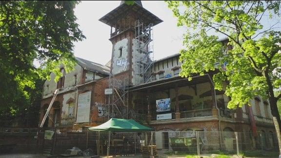 Insel Peißnitz in Halle/Saale. Baufälliger Gebäudekomplex, der gerade renoviert wird, mit kleinem Türmchen.