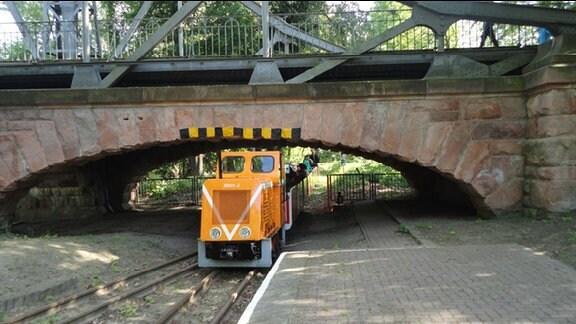 Kleine Parkeisenbahn mit orangefarbener Lok fährt unter einer Brücke hindurch.