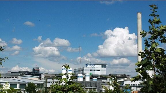 Blick auf den Standort des Glaswerkes Schott in Jena. Zwischen den Gebäuden stehen mehrere Silos. Rechts im Bild steht ein hoher Schornstein. Am größten Gebäude ist das Logo Schott zu sehen. Im Hintergrund ist noch der Jentower zu erkennen.