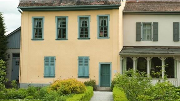 Schillerhaus in Jena. Ehemaliges, renoviertes, dreistöckiges, Bauernhaus mit gelber Fassade und grünen Fensterrahmen.