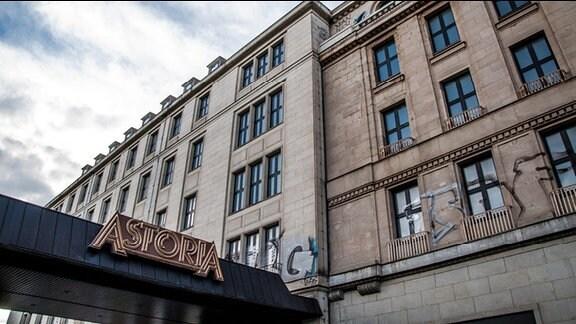 """Ehemaliges Hotel """"Astoria"""" in Leipzig. Im Vordergrund überdachter Eingang zum Hotel mit dem Schriftzug """"Astoria"""". Das ungenutzte Gebäude ist mit Graffiti beschmiert."""